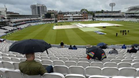 Spectators shelter from the rain at Lord's