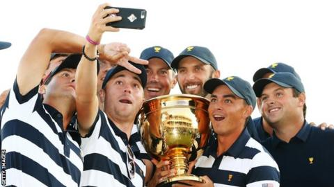 The U.S. Team celebrates with the trophy after they defeated the International Team 19 to 11 in the Presidents Cup at Liberty National Golf Club on October 1, 2017 in Jersey City, New Jersey.