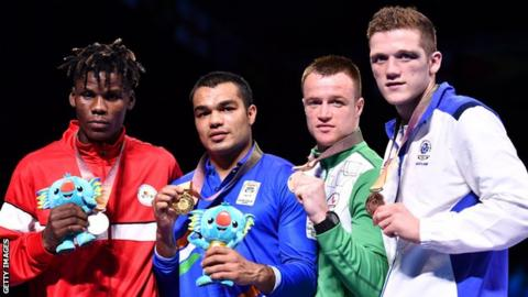 Silver medallist Cameroon's Dieudonne Wilfried Seyi Ntsengue, gold medallist India's Vikas Krishan and bronze medallists Northern Ireland's Steven Donnelly and Scotland's John Docherty pose during the medal ceremony for the men's 75kg boxing event during the 2018 Gold Coast Commonwealth Games at the Oxenford Studios venue on the Gold Coast on April 14