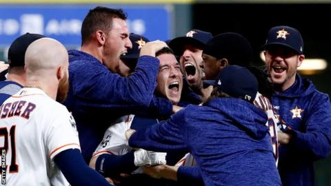 Alex Bregman is mobbed by team-mates after giving the Astros victory