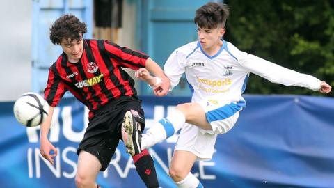 Dean Morgan of Crusaders in action against Newry's Tiernan Hughes during the Under-15 Rosebowl final which the Crues won 3-0