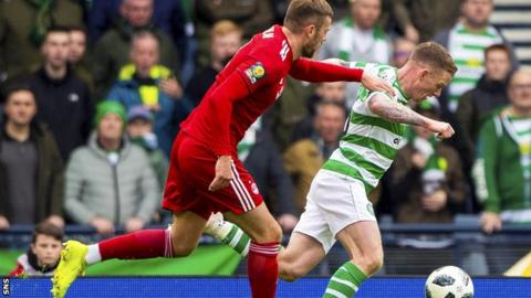 Celtic winger Jonny Hayes goes down under the challenge of Aberdeen's Mikey Devlin to win a penalty