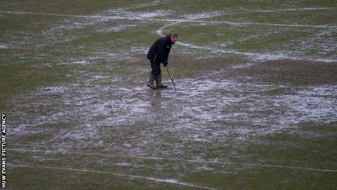 A groundsman battles with standing water on the Rodney Parade pitch in Newport