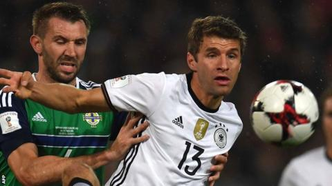 Northern Ireland defender Gareth McAuley challenges Thomas Muller of Germany