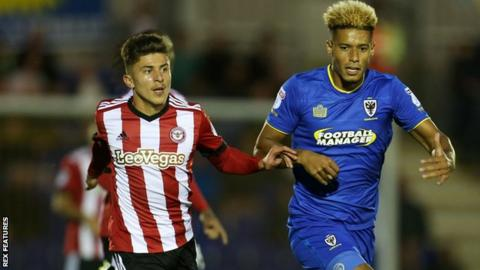 Brentford defender Ilias Chatzitheodoridis and AFC Wimbledon striker Lyle Taylor compete for the ball