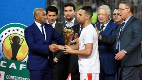 "Zamalek player Hazem Emam (C) receives the trophy from the president of the African Football Federation Ahmed Ahmed (L) after they won the CAF Confederation Cup final football match between Egypt""s Zamalek and Morocco""s RSB Berkane at Borg El Arab Stadium near Alexandria"