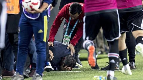 Besiktas boss Senol Gunes holds his head after being struck by an object from the crowd