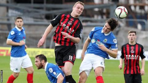 Jordan Owens of Crusaders and Linfield's Jimmy Callacher in aerial action