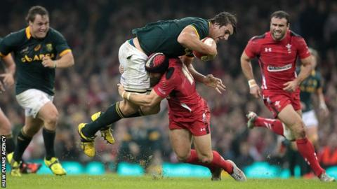Eben Etzebeth of South Africa is taken down by Leigh Halfpenny of Wales