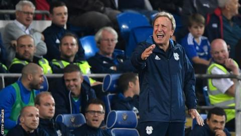 Neil Warnock shouts and gesticulates with his right hand from the touchline during a Cardiff City game