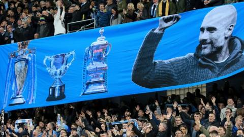 City fans display a banner celebrating Guardiola's trophy successes with the club