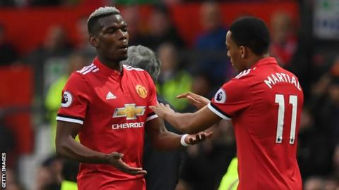 Manchester United midfielder Paul Pogba taps hands with Anthony Martial as he is replaced