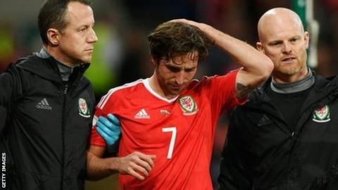 Joe Allen was led off by Wales medical officer Dr Jonathan Houghton (left) and physio Sean Connelly