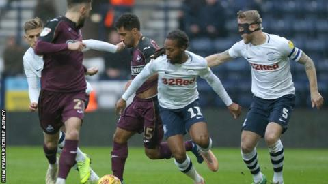 Wayne Routledge of Swansea is tackled by Daniel Johnson of Preston North End and Tom Clarke of Preston North End