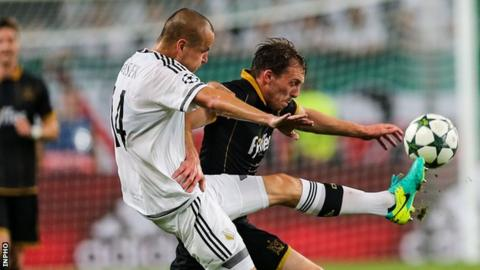Adam Hlousek and David McMillan challenge for the ball in Warsaw