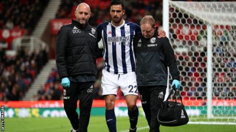 Nacer Chadli is helped off the pitch after being injured.