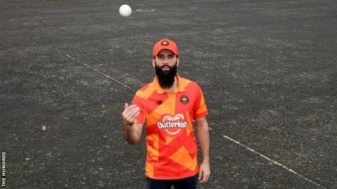 Birmingham Phoenix captain Moeen Ali tosses a ball in the air while wearing his team's shirt and cap