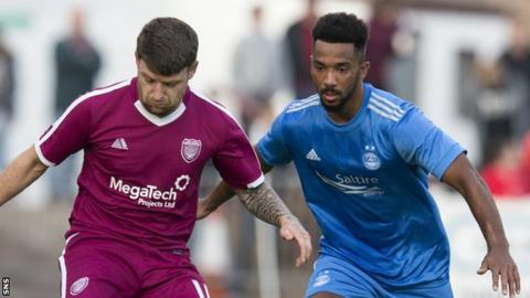 Aberdeen defender Shay Logan moves in to tackle Arbroath's Bobby Linn