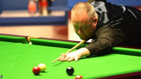 John Higgins plays a shot