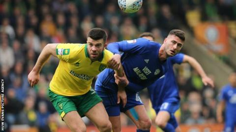 Gary Madine of Cardiff City and Grant Hanley of Norwich City look to win the ball