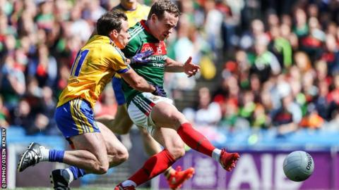 Andy Moran scores Mayo's third goal despite pressure from Roscommon's Niall Kilroy.