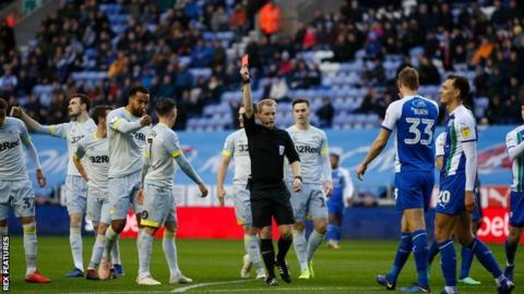 Referee Gavin Ward shows a red card to Wigan midfielder Kal Naismith in the 15th minute