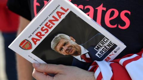 Arsenal fan holding the match day programme