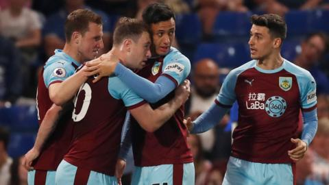 Burnley's players celebrate scoring at Chelsea