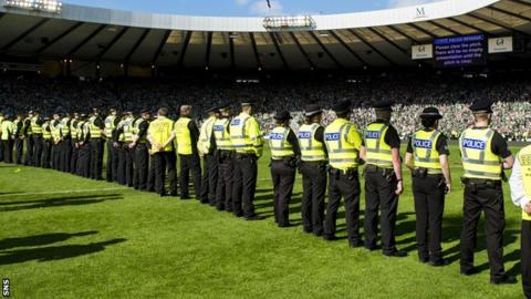 Police stand guard on the Hampden pitch