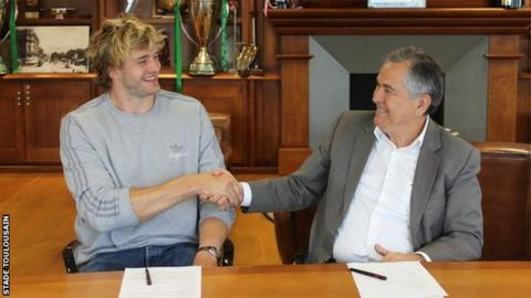 Richie Gray shakes hands with Toulouse president Jean-Rene Bouscatel after signing his deal