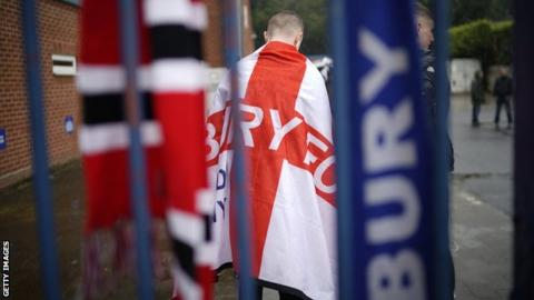 Bury fan stands at the gates of Gigg Lane