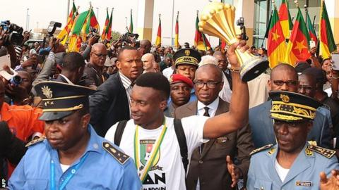 Cameroon's players were welcomed by fans at the airport on their return from Gabon on Monday