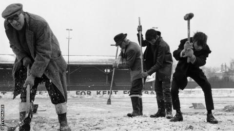 Workers in 1963 try and clear of football pitch full of snow