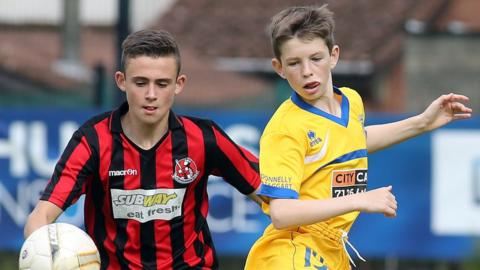 Ross Ferguson of Crusaders in action against Trojans player Aiden Rakin in the Under-15 section of the Foyle Cup