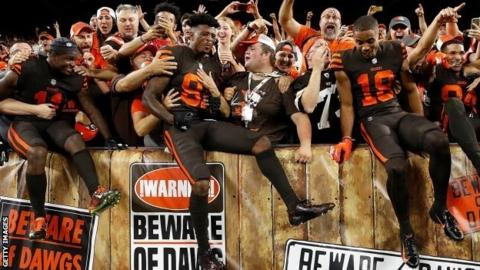 Cleveland Browns players celebrate with fans