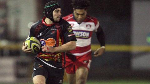 Dragons player Adam Hughes scoring a try against Gloucester