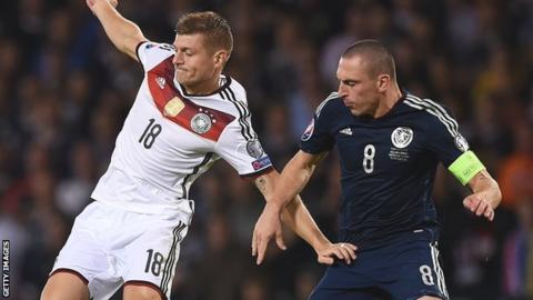 Toni Kroos of Germany is challenged by Scotland captain Scott Brown