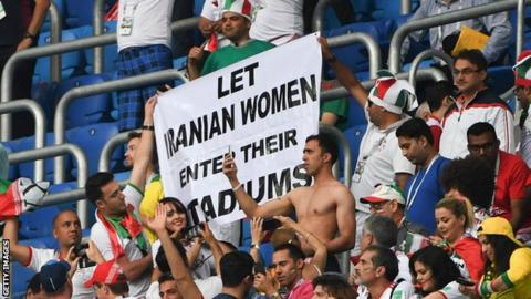 "A campaign group holds up a banner saying ""Let Iranian women enter their stadiums"" at a match between Morocco and Iran at the 2018 World Cup"