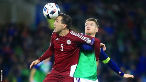 Latvia's Ojeg Laizans contends for possession with NI captain Steven Davis