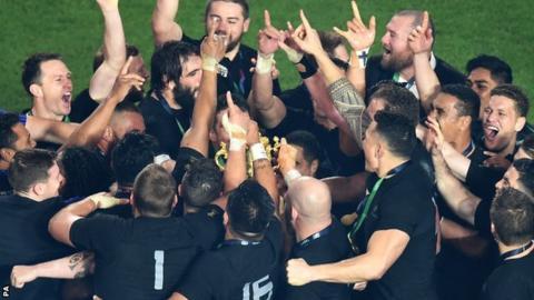 New Zealand huddle round the Webb Ellis Cup