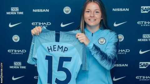 Lauren Hemp holds up a Manchester City shirt after her unveiling