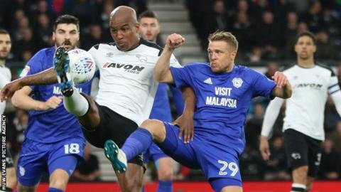 Andre Wisdom of Derby County and Jamie Ward of Cardiff City compete for the ball