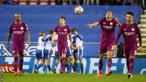 Man City players look dejected during their fifth round defeat to Wigan 12 months ago