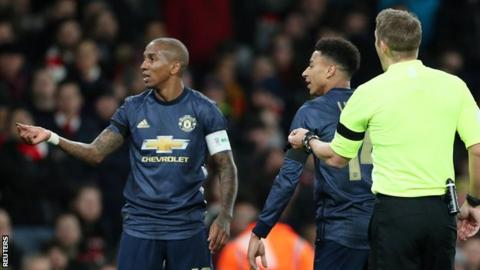 Ashley Young picked up a coin and held it towards the Arsenal fans during his side's FA Cup win at Arsenal