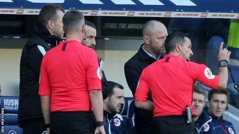 Keith Stroud speaks with both managers during a halt in Millwall's win against Reading