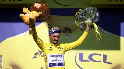 Julian Alaphilippe raises his hands in celebration on the podium after winning stage 13 of the 2019 Tour de France