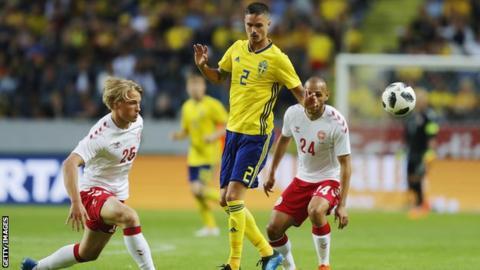 Sweden's Mikael Lustig competes for the ball against Denmark's Martin Braithwaite and Kasper Dolberg