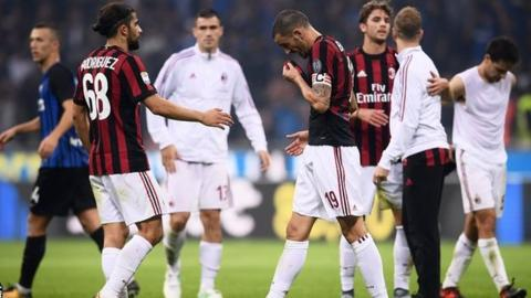 AC Milan players react at the end of their 3-2 defeat to Inter Milan