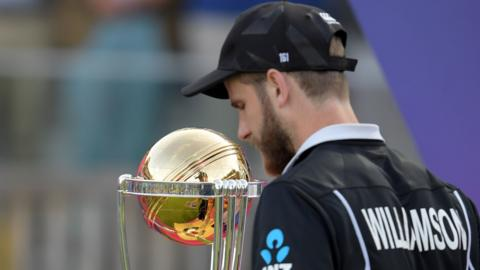 Kane Williamson walks past World Cup trophy