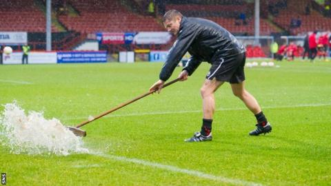 Groundsman at Firhill mops up surface water